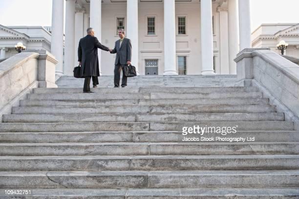 Businessman shaking hands on steps