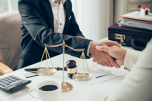Businessman shaking hands to seal a deal with his partner lawyers or attorneys discussing a contract agreement 930579260