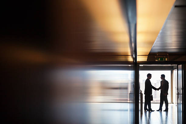 Businessman shaking hands together in corridor