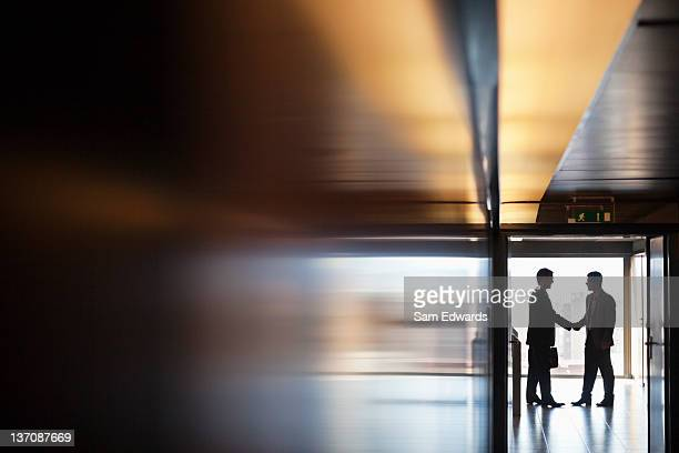 businessman shaking hands together in corridor - focus on background stock pictures, royalty-free photos & images