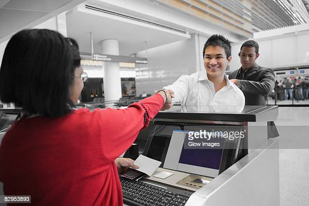 Businessman shaking hands with an airline check-in attendant