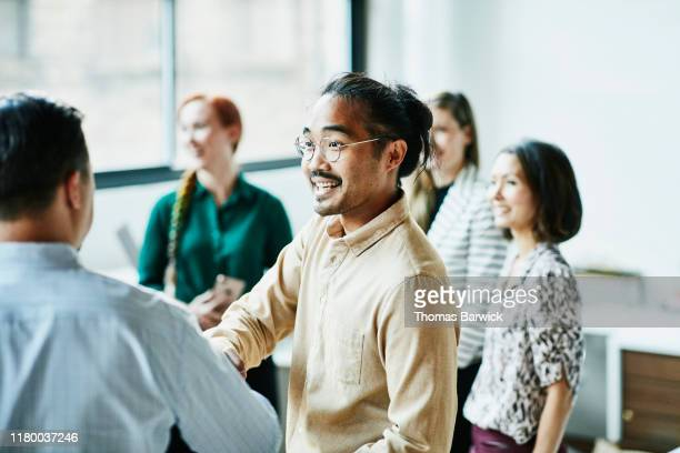 businessman shaking hands with colleague after meeting in office - multi etnische groep stockfoto's en -beelden
