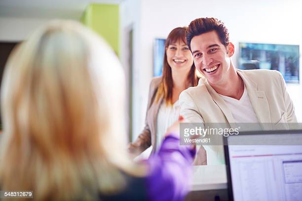 Businessman shaking hands with hotel staff at reception