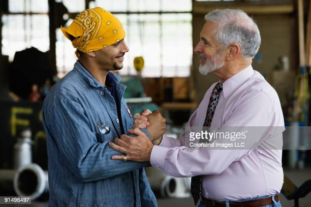 Businessman shaking hands with male warehouse worker