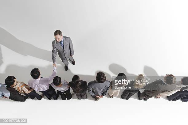 Businessman shaking hands with row of colleagues, elevated view