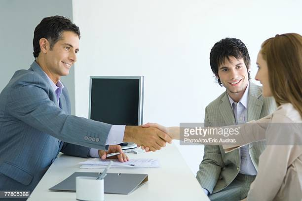 Businessman shaking hands with young woman across desk, young woman's male companion smiling