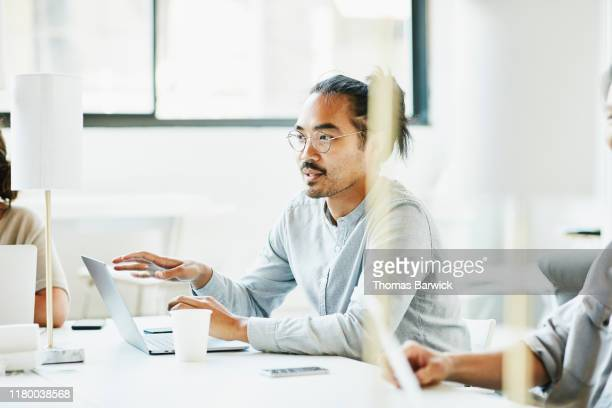 businessman sharing ideas during team meeting in office conference room - selective focus photos et images de collection