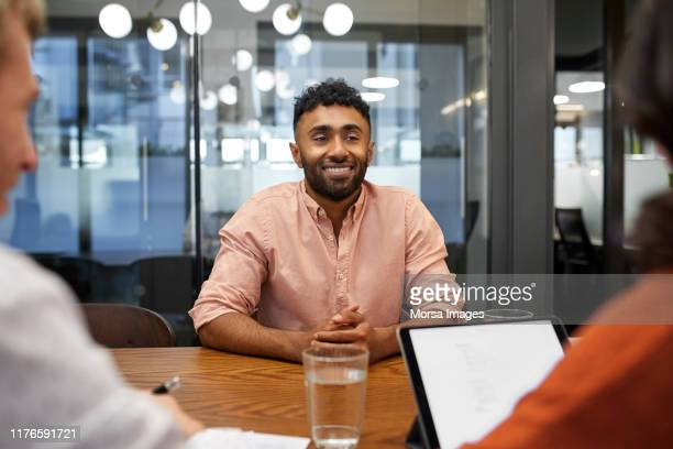 businessman sharing ideas with colleagues - conference table stock pictures, royalty-free photos & images