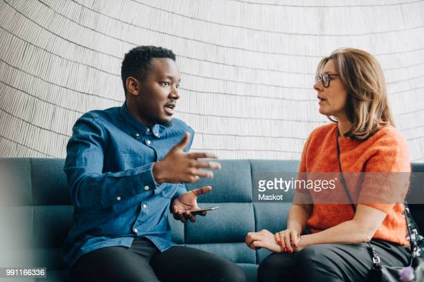 businessman sharing ideas with female colleague while sitting on couch at conference - expliquer photos et images de collection