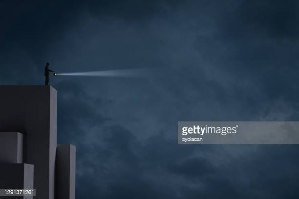 businessman sheds light on the darkness - syolacan stock pictures, royalty-free photos & images