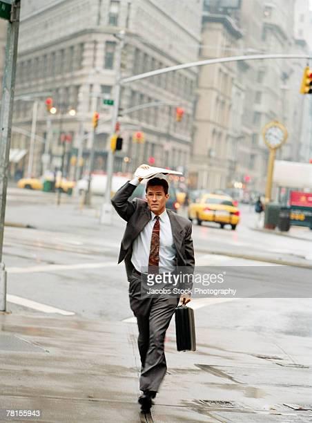 Businessman shielding himself during a downpour