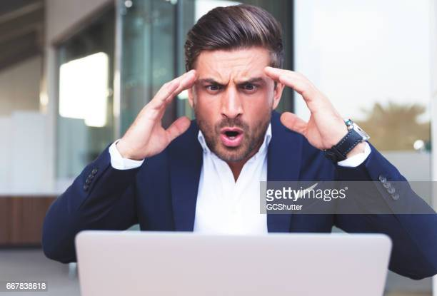 businessman shocked after reading a news on his laptop - geschokt stockfoto's en -beelden