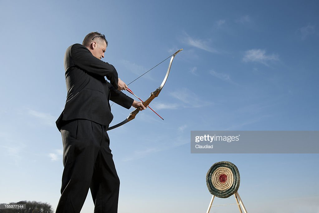 Businessman shooting on target : Stock Photo