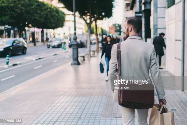 businessman shopping after work - shoulder bag stock pictures, royalty-free photos & images