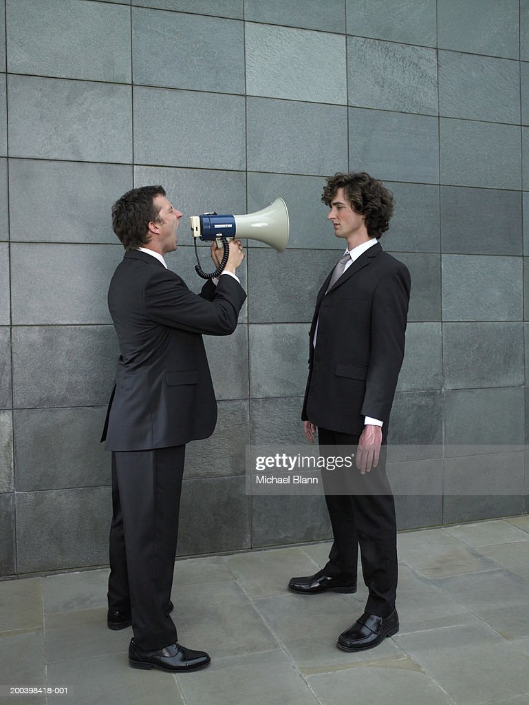 Businessman shouting at yonger colleague through megaphone, side view : Stock Photo