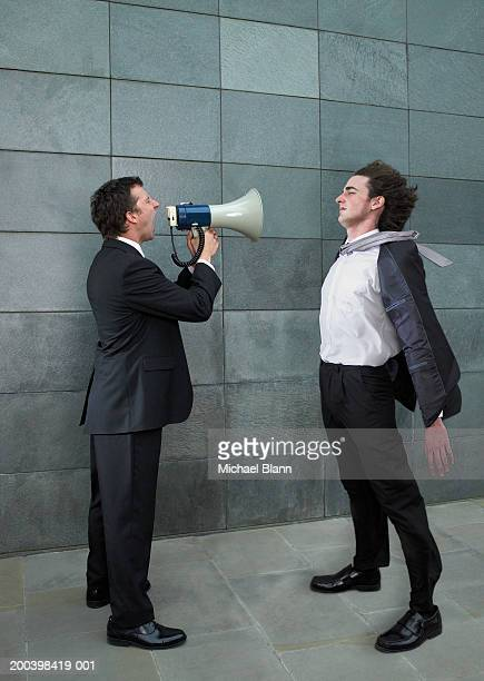 Businessman shouting at yonger colleague through megaphone, side view