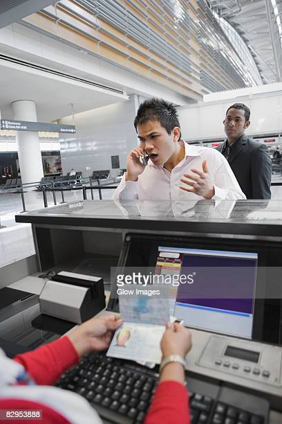 Businessman shouting in a mobile phone at a ticket counter in an airport