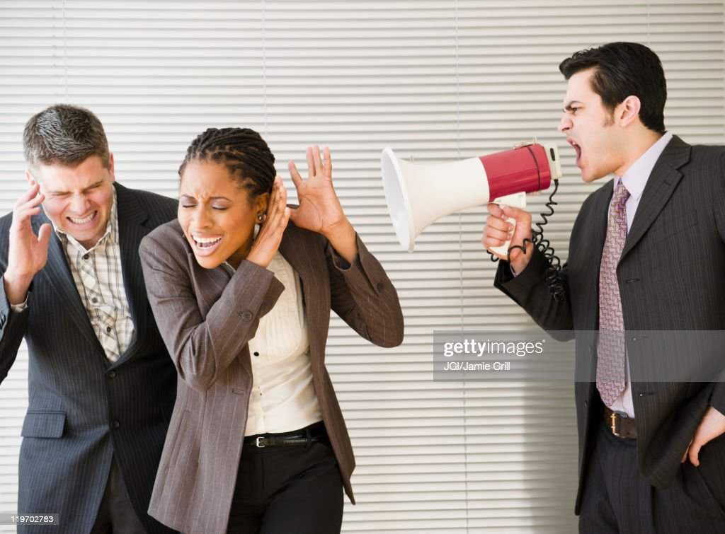 Businessman shouting through bullhorn at co-workers : Stock Photo