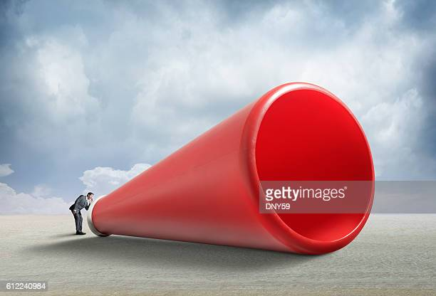 Businessman Shouts Into A Large Oversized Megaphone