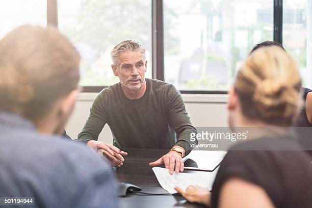 businessman showing a document to his colleagues - four people stock pictures, royalty-free photos & images