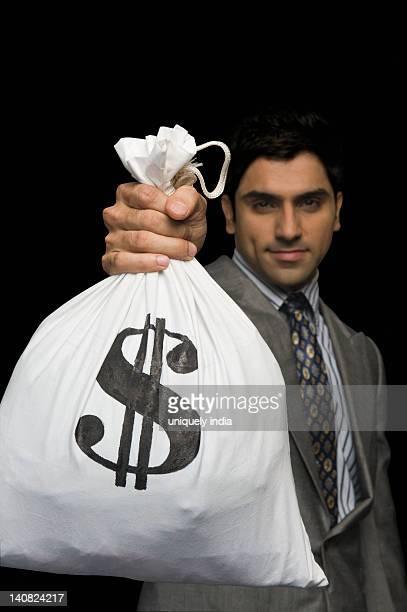 Businessman showing a money bag