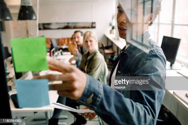 businessman showing adhesive note to creative team seen from glass at workplace - adulte d'âge moyen photos et images de collection