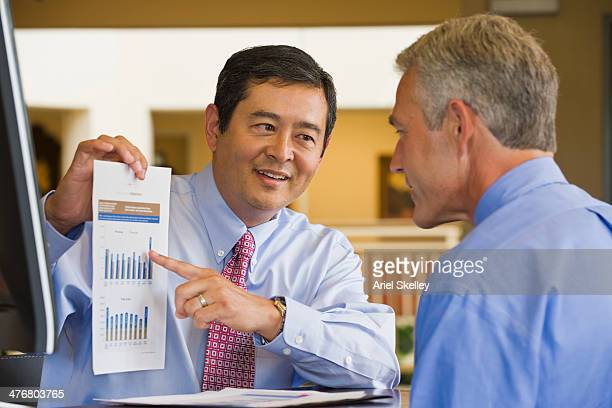 Businessman showing chart to co-worker