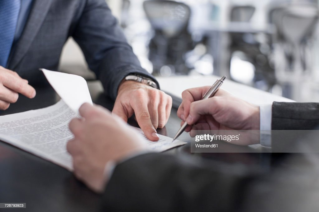 Businessman showing client where to sign document : Stock Photo