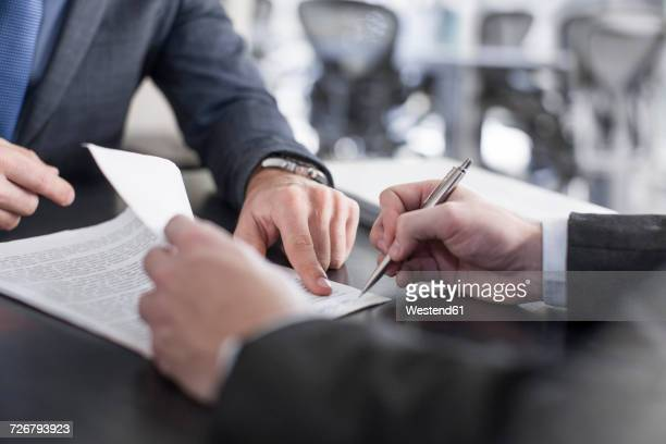 businessman showing client where to sign document - abmachung stock-fotos und bilder