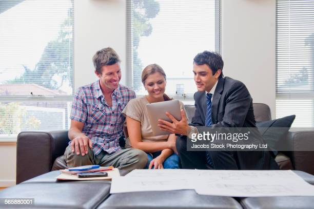 Businessman showing clients paperwork in living room