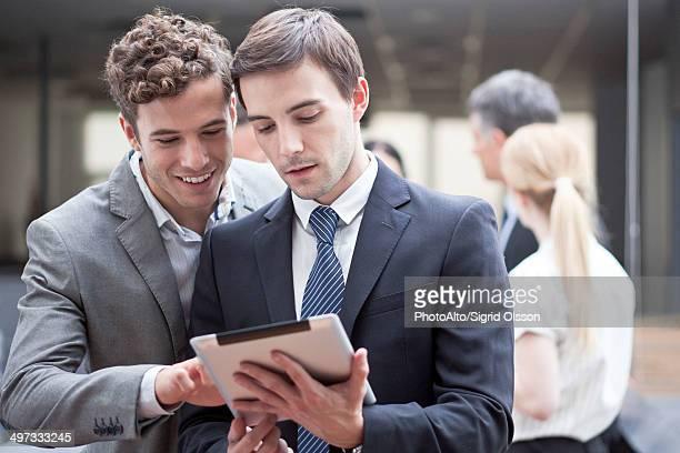 Businessman showing colleague digital tablet