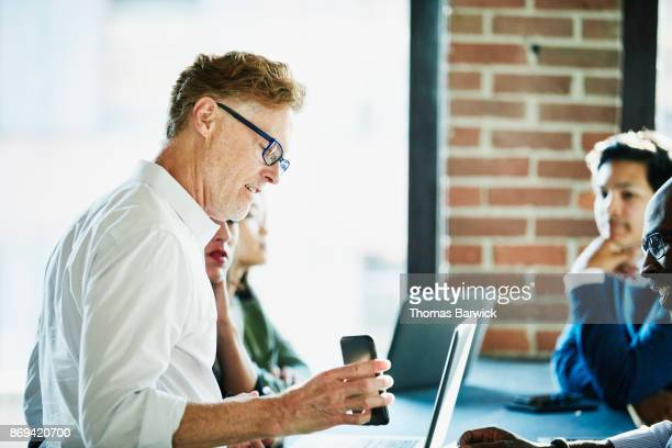 Businessman showing data on smartphone to coworkers during meeting in high tech office