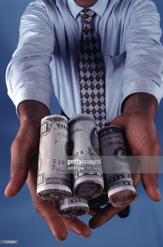 businessman showing dollar rolls : Stock Photo