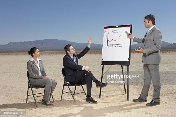 Businessman showing graph  to colleagues, man raising hand