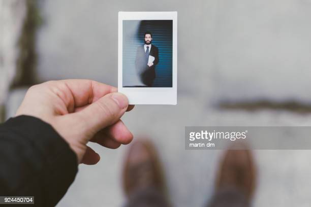 Businessman showing instant portrait