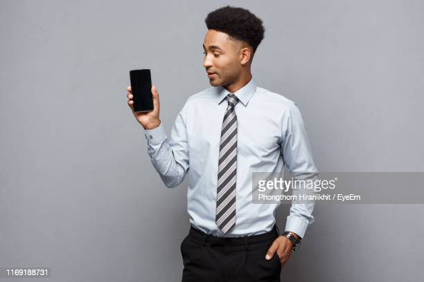 businessman showing mobile phone screen while standing against gray background - overhemd en stropdas stockfoto's en -beelden
