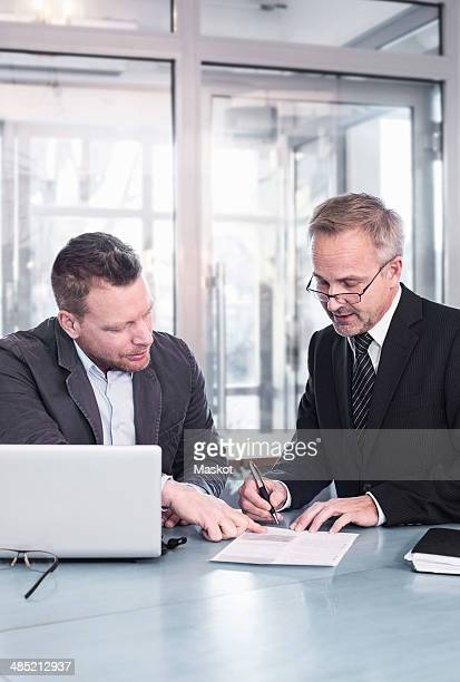 Businessman showing partner to sign document at restaurant table