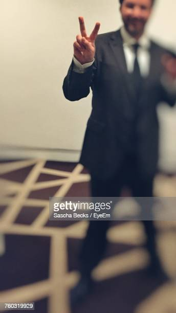 Businessman Showing Peace Sign While Standing At Office