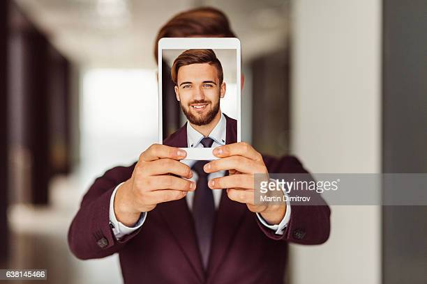 businessman showing selfie on tablet - obscured face stock pictures, royalty-free photos & images