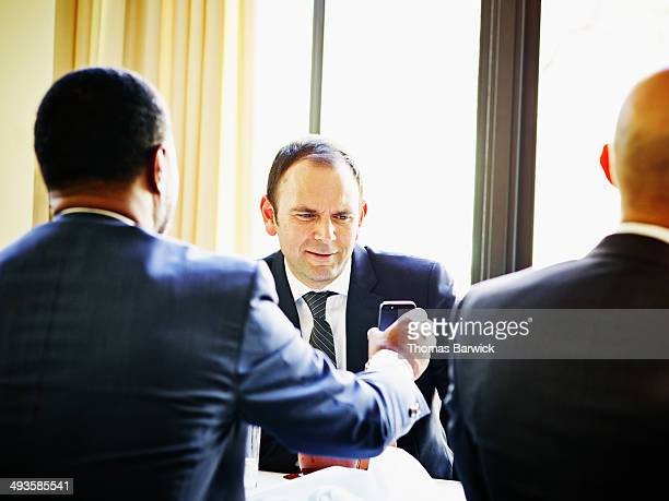 Businessman showing smart phone to colleague