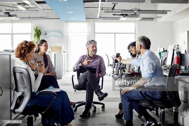 businessman showing smart phone to colleagues - latin america stock pictures, royalty-free photos & images