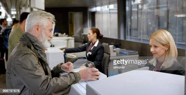 Businessman showing smart phone to customer service representative at ticket counter