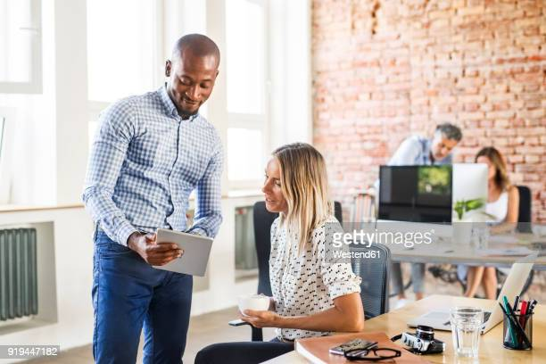 Businessman showing tablet to colleague at desk in office