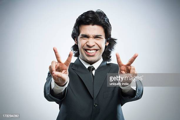 Businessman showing victory sign with his both hands