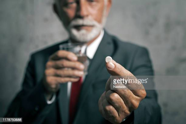 businessman showing white pill - aspirin stock pictures, royalty-free photos & images