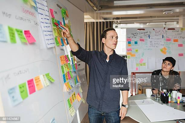 Businessman showing whiteboard and explaining colleagues during meeting in office