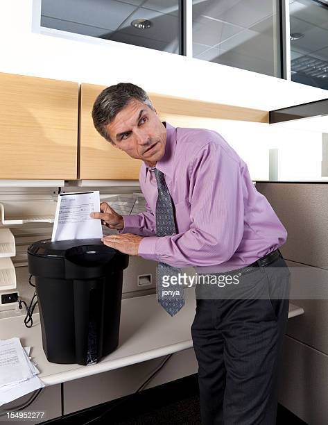 businessman shredding confidential papers