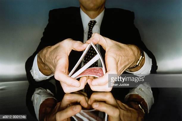 businessman shuffling cards - barajar fotografías e imágenes de stock