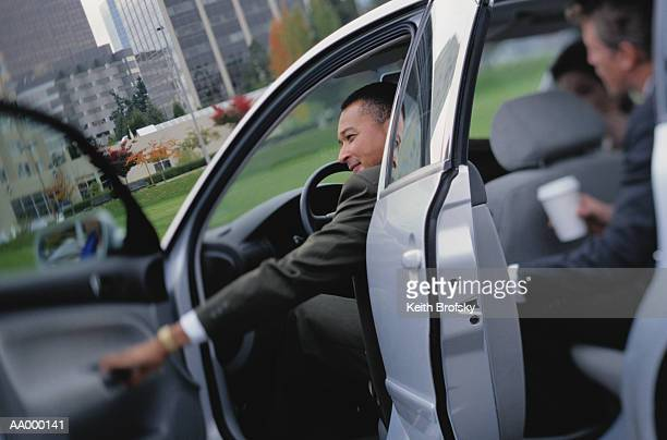businessman shutting his car door - car pooling stock photos and pictures
