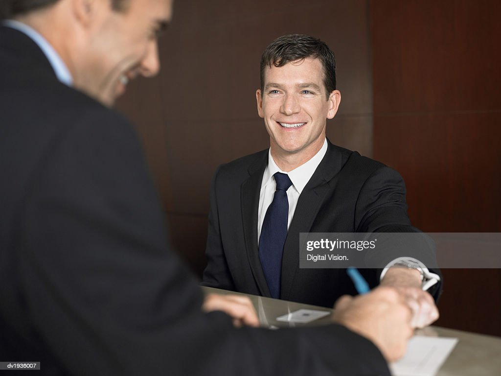 Businessman Signing a Document at a Reception Desk : Stock Photo
